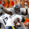 Oklahoma State\'s Anthony Rogers (94) pressures West Virginia\'s Geno Smith (12) during a college football game between Oklahoma State University (OSU) and the West Virginia University at Boone Pickens Stadium in Stillwater, Okla., Saturday, Nov. 10, 2012. OSU won 55-34. Photo by Sarah Phipps, The Oklahoman