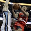 Photo - Portland Trail Blazers' Damian Lillard (0) drives to the basket in front of Memphis Grizzlies' Marc Gasol, of Spain, left, during first half of an NBA basketball game in Memphis, Tenn., Wednesday, March 6, 2013. (AP Photo/Daniel Johnston)