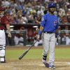 Photo - Chicago Cubs' Arismendy Alcantara, right, leaves the home plate area after striking out as Arizona Diamondbacks' Miguel Montero, left, heads back to the dugout during the third inning of a baseball game on Sunday, July 20, 2014, in Phoenix. (AP Photo/Ross D. Franklin)