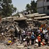 People gather around a heap of debris at the site of a building collapsed as a rescue operation continues on the outskirts of Mumbai, India, Friday, April 5, 2013. A half-finished building that was being constructed illegally in a suburb of India\'s financial capital collapsed, killing 35 people and injuring more than 50 others, police said Friday. (AP Photo/Rajanish Kakade)