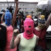 Russian punk group Pussy Riot members Nadezhda Tolokonnikova, in the blue balaclava, and Maria Alekhina, in the pink balaclava, make their way through a crowd after they were released from a police station, Tuesday, Feb. 18, 2014, in Adler, Russia. No charges were filed against Tolokonnikova and Alekhina along with the three others who were detained. (AP Photo/Morry Gash)