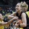 Stanford forward Mikaela Ruef, center, is double-teamed under the basket by Oregon\'s Devyn Galland, left, and Jillian Alleyne during the first half of an NCAA college basketball game in Eugene, Ore., Friday, Feb. 1, 2013. (AP Photo/Don Ryan)