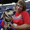 Photo - Stephanie Poynter and her pet dachshund Charlie wait for the Atlanta Braves and Oakland Athletics to begin during the team's Bark in the Park promotion where dog owners are allowed to bring their canines to a baseball game Sunday, Aug. 17, 2014, in Atlanta. (AP Photo/David Tulis)