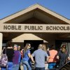 Photo -  A crowd gathers outside during a Noble Board of Education meeting to decide Noble Public Schools Superintendent Ronda Bass' employment status in Noble, Okla., Tuesday, Sept. 2, 2014. Bass came under fire for her alleged inappropriate enforcement of the school's dress code. Photo by Bryan Terry, The Oklahoman   Bryan Terry -  THE OKLAHOMAN