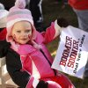 Twenty-month-old Lexie Lorton holds a sign supporting the Oklahoma Sooners while sitting in a small covered wagon pulled by her dad, Jay Lorton. The Lortons live in Tulsa. ESPN broadcast their weekly pre-game sports show, GameDay, from the the campus of the University of Oklahoma, Saturday morning, Oct. 27, 2012. The network\'s broadcast crew is in Norman for the OU - Notre Dame football game Saturday night. Several thousand OU fans and a smattering of Notre Dame supporters , many carrying homemade signs, crowded around the stage to watch the live broadcast. Photo by Jim Beckel, The Oklahoman