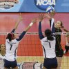 Oregon\'s Alaina Bergsma, facing, attempts to hit over the defense of Penn State\'s Nia Grant, left, and Ariel Scott during the national semifinals of the NCAA college women\'s volleyball tournament Thursday, Dec. 13, 2012 in Louisville, Ky. (AP Photo/Timothy D. Easley)