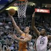 Photo -   Phoenix Suns point guard Goran Dragic, center, of Slovenia, lays the ball up as Utah Jazz power forward Derrick Favors (15) defends in the first quarter during an NBA basketball game on Saturday, Nov. 10, 2012, in Salt Lake City. (AP Photo/Rick Bowmer)