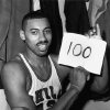 "Photo - In this March 2, 1962 file photo, Wilt Chamberlain of the Philadelphia Warriors holds a sign reading ""100"" in the dressing room in Hershey, Pa., after he scored 100 points,  as the Warriors defeated the New York Knickerbockers 169-147. For 50 years, Chamberlain's 100-point night has stood as one of sports magic numbers. (AP Photo/Paul Vathis, File)"