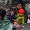 An Indian woman carries children and sits beside her roadside shanty on a cold winter morning in Kolkata, India, Friday, Jan. 11, 2013. More than 100 people have died of exposure as several parts of India deal with historically cold temperatures. (AP Photo/Bikas Das)