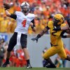 Oklahoma State quarterback J.W. Walsh (4) attempts a pass as West Virginia\'s Brandon Golson rushes in during the second quarter of an NCAA college football game in Morgantown, W.Va., on Saturday, Sept. 28, 2013. (AP Photo/Tyler Evert) ORG XMIT: WVTE103