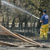 A Jones firefighter sprays hot spots near Britton road and Prosper drive after wildfires swept through the area in Oklahoma City , Wednesday, August 31, 2011. Photo by Steve Gooch, The Oklahoman