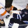 Philadelphia Flyers\' Tye McGinn (15) fights with Winnipeg Jets\' Mark Stuart (5) during the second period of an NHL hockey game in Winnipeg, Manitoba, Tuesday, Feb. 12, 2013. (AP Photo/The Canadian Press, Trevor Hagan)