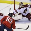 Photo - Phoenix Coyotes goalie Mike Smith (41) deflects the puck shot  by Washington Capitals Jay Beagle (83) as Coyotes' Derek Morris (53) defends during the second period of an NHL hockey game, Saturday, March 8, 2014, in Washington. (AP Photo/Carolyn Kaster)