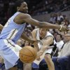 San Antonio Spurs\' Manu Ginobili, right, of Argentina, passes the ball under the arm of Denver Nuggets\' Kenneth Faried, left, during the first half of an NBA basketball game, Wednesday, March 27, 2013, in San Antonio. (AP Photo/Eric Gay)