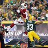 Photo - Arizona Cardinals' Jaron Brown catches a touchdown pass in front of Green Bay Packers' Micah Hyde (33) during the first half of a preseason NFL football game Friday, Aug. 9, 2013, in Green Bay, Wis. (AP Photo/Mike Roemer)