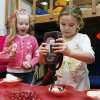 First-grader Bonnie King. 6, watches her classmate Jane Mikkelson, 6, as she works on her ice cream sundae during their class Valentine\'s Day party at Chisholm Elementary School in Edmond, OK, Friday, Feb. 13, 2009. BY PAUL HELLSTERN, THE OKLAHOMAN