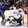 Nashville Predators\' Joel Ward, right, falls on Vancouver Canucks\' goalie Roberto Luongo as Canucks\' Keith Ballard, left, watches during the first period of an NHL hockey game in Vancouver, British Columbia, on Wednesday, Jan. 26, 2011. (AP Photo/The Canadian Press, Darryl Dyck)