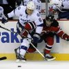 New Jersey Devils\' Adam Henrique, right, battles along the boards with Tampa Bay Lightning\'s Sami Salo, of Finland, during the first period of an NHL hockey game Tuesday, March 5, 2013, in Newark, N.J. (AP Photo/Bill Kostroun)