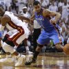 Miami Heat shooting guard Dwyane Wade (3) and Oklahoma City Thunder shooting guard Thabo Sefolosha (2) of Switzerland go after a loose ball during the second half at Game 3 of the NBA Finals basketball series, Sunday, June 17, 2012, in Miami. Miami won 91-85. (AP Photo/Lynne Sladky) ORG XMIT: NBA155