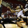 Photo - UCLA guard Nirra Fields, right, goes down after being fouled by Colorado forward Jamee Swan, lower left, in the first half of an NCAA college basketball game in the Pac-12 women's tournament, Thursday, March 6, 2014, in Seattle. (AP Photo/Ted S. Warren)