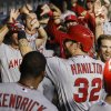 Los Angeles Angels\' Josh Hamilton (32) is greeted by teammates in the dugout after hitting a solo home-run against the Texas Rangers during the seventh inning of a baseball game, Wednesday, July 31, 2013, in Arlington, Texas. (AP Photo/Jim Cowsert)