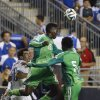 Photo - Nigeria defenders Kenneth Omeruo (22) and Efe Ambrose (5) leaps for a header against Greece midfielder Lazaros Christodoulopoulos (16) during the second half of an international friendly soccer match, Tuesday, June 3, 2014, in Chester, Pa. The match ended in a tie, 0-0. (AP Photo/Matt Slocum)