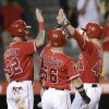 Photo - Los Angeles Angels' Mark Trumbo, right, is congratulated by Josh Hamilton, left, and Kole Calhoun after hitting a three-run home run against the Texas Rangers during the fourth inning of a baseball game on Friday, Sept. 6, 2013, in Anaheim, Calif. (AP Photo/Jae C. Hong)