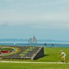 Photo - In this undated file photo provided by the Traverse City Tourism, people enjoy a summer day in the Open Space park by Grand Traverse Bay in Traverse City, Mich. Some local residents say festivals occupy the park too much in summer, while others say it's a reasonable price to pay for a strong tourism economy. (AP Photo/Traverse City Tourism)