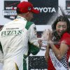 Photo - Winner Mike Conway, left, of England sprays Clarissa Burquez, Miss Grand Prix of Long Beach runner-up, with sparkling wine on the podium after the IndyCar Grand Prix of Long Beach auto race on Sunday, April 13, 2014, in Long Beach, Calif. (AP Photo/Alex Gallardo)