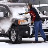 A man brushes snow from his car\'s windshield after Sunday services at Cornerstone Church in Midwest City. Snow began falling in central Oklahoma around 7 Sunday morning, Feb. 2, 2014. Photo by Jim Beckel, The Oklahoman