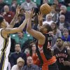 Photo - Utah Jazz's Diante Garrett, left, and Toronto Raptors' Chuck Hayes (44) reach for the ball as Toronto Raptors' Amir Johnson (15) looks on in the second quarter of an NBA basketball game, Monday, Feb. 3, 2014, in Salt Lake City.  (AP Photo/Rick Bowmer)