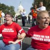 Women link arms and sit in a circle Thursday to block the intersection of Independence Avenue SE and New Jersey Avenue SE outside the House of Representatives on Capitol Hill in Washington. They were protesting Congress' inaction on comprehensive and inclusive immigration reform. AP Photo