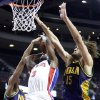 Photo - Detroit Pistons guard Rodney Stuckey (3) is defended while going to the basket by New Orleans Hornets forward Anthony Davis, left, and center Robin Lopez (15) in the first half of an NBA basketball game, Monday, Feb. 11, 2013, in Auburn Hills, Mich. (AP Photo/Duane Burleson)