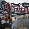 Onlookers observe a mangled crane at the construction site in the Queens borough of New York where it collapsed, Wednesday, Jan. 9, 2013 behind a big neon