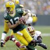 Photo - Washington Redskins' Josh Wilson sacks Green Bay Packers quarterback Aaron Rodgers during the second half of an NFL football game Sunday, Sept. 15, 2013, in Green Bay, Wis. (AP Photo/Tom Lynn)