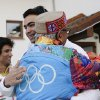 Indian luger Shiva Keshavan, center, facing camera, is hugged by supporter Omprakash Mundra after a welcome ceremony for the Indian Olympic team at the Mountain Olympic Village during the 2014 Winter Olympics, Sunday, Feb. 16, 2014, in Krasnaya Polyana, Russia. (AP Photo/Jae C. Hong)