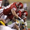 Oklahoma\'s Travis Lewis (28) and Demontre Hurst (6) bring down Iowa\'s Jordan Canzeri (33) during the Insight Bowl college football game between the University of Oklahoma (OU) Sooners and the Iowa Hawkeyes at Sun Devil Stadium in Tempe, Ariz., Friday, Dec. 30, 2011. Photo by Bryan Terry, The Oklahoman