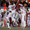Oklahoma\'s Frank Alexander (84), Oklahoma\'s Quinton Carter (20) and Marcus Trice (13) celebrate a interception with a coach during the Bedlam college football game between the University of Oklahoma Sooners (OU) and the Oklahoma State University Cowboys (OSU) at Boone Pickens Stadium in Stillwater, Okla., Saturday, Nov. 27, 2010. Photo by Sarah Phipps, The Oklahoman