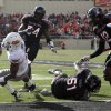 Oklahoma State Cowboys\'s Joseph Randle (1) scores a touchdown in front of Texas Tech\'s Dartwan Bush (54), Cqulin Hubert (51) and D.J. Johnson (12) during a college football game between Texas Tech University (TTU) and Oklahoma State University (OSU) at Jones AT&T Stadium in Lubbock, Texas, Saturday, Nov. 12, 2011. Photo by Sarah Phipps, The Oklahoman ORG XMIT: KOD