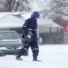 COLD WEATHER / WINTER STORM / SNOW / POSTAL CARRIER / MAILMAN / POSTMAN: Mail carrier David Alexander lowers his head and walks through snow delivering mail in a Midwest City neighborhood near SE 15 and Lockheed. Alexander, who has worked for the post office for 26 years, said the most difficult part of delivering the mail in this weather is walking through the snow. He said the sub-freezing temperatures don\'t bother him too much because he dresses for the cold. He wears five layers of clothing above the waist and three layers of clothing below the waist. He wears thermal undershirts and pants. On his feet, he wears boots. He wears gloves and a mask around his face. A second winter storm in a week dumped about 6 inches of snow in the Oklahoma City area Tuesday morning, Feb. 9, 2011. Photo by Jim Beckel, The Oklahoman ORG XMIT: KOD