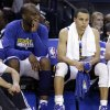 Golden State Warriors\' Carl Landry, left, and Stephen Curry watch from the bench during the second half of an NBA basketball game against the Oklahoma Thunder Thursday, April 11, 2013, in Oakland, Calif. (AP Photo/Ben Margot)