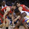 Portland Trail Blazers\' Joel Freeland, left, Victor Claver (18), and Golden State Warriors\' Harrison Barnes chase a loose ball during the first half of an NBA basketball game Friday, Jan. 11, 2013, in Oakland, Calif. (AP Photo/Ben Margot)