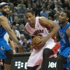 Photo - Toronto Raptors forward DeMar DeRozan, center, drives the middle past Dallas Mavericks forwards Vince Carter, left, and Jae Crowder during the first half of an NBA basketball game, Wednesday, Jan. 22, 2014 in Toronto.   (AP Photo/The Canadian Press, Nathan Denette)