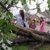 Photo - Seventeen year-old Deanna Locke and her siblings including, from left, Charlotte, 13; Drew, 9; and Trinity, 11; examine a downed tree across the street from their home in Tupelo, Miss., after a suspected tornado moved through town earlier on Monday, April 28, 2014.( AP Photo/Jim Lytle)