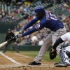 Texas Rangers\' Jurickson Profar singles in a run as Seattle Mariners catcher Kelly Shoppach watches in the first inning of a baseball game Saturday, May 25, 2013, in Seattle. (AP Photo/Elaine Thompson)
