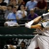 Photo -   Oakland Athletics' George Kottaras (14) connects for a solo home run off of Texas Rangers' Mark Lowe in the 10th inning of a baseball game, Tuesday, Sept. 25, 2012, in Arlington, Texas. The Athletics won 3-2. (AP Photo/Tony Gutierrez)