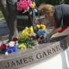 Katrina Prince, a fan of James Garner and Norman resident, places flowers on the statue of James Garner on Main St. in downtown Norman, Okla., Sunday, July 20, 2014. Garner died Saturday at age 86. Photo by Nate Billings, The Oklahoman
