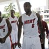 Photo - LeBron James, right, Dwyane Wade and Chris Bosh arrive for interviews during Media Day on Monday. AP PHOTO