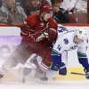 Photo - Vancouver Canucks' Alex Burrows (14) and Phoenix Coyotes' Shane Doan, left, collide as they go after the puck during the first period of an NHL hockey game on Tuesday, March 4, 2014, in Glendale, Ariz. (AP Photo/Ross D. Franklin)