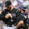 Photo - Colorado Rockies starting pitcher Jordan Lyles, left, talks with catcher Michael McKenry after giving up a two-run home run to Cincinnati Reds' Jay Bruce in the fourth inning of a baseball game in Denver on Sunday, Aug. 17, 2014. (AP Photo/David Zalubowski)